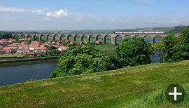 A train heads south across the Royal Border Bridge at Berwick upon Tweed