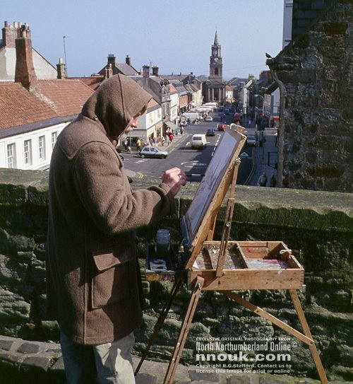 An artist at work on the walls overlooking the main street at Berwick upon Tweed. The town was painted by the famous L.S.Lowry too.