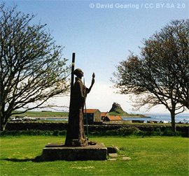 Statue of St. Aidan with Lindisfarne castle in the background